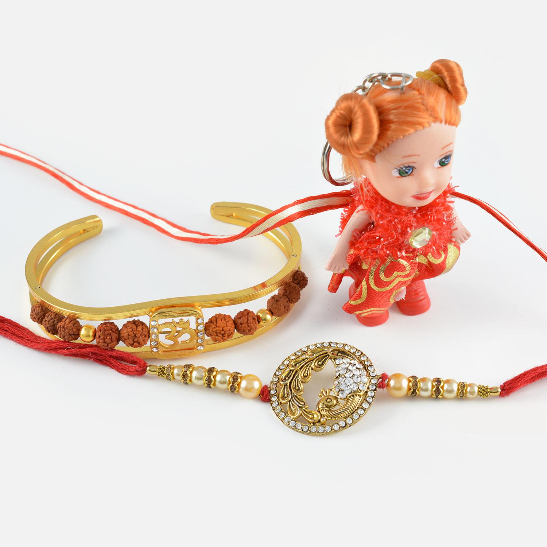 Golden Diamond Studded Peacock and Divine Rudraksha Bracelet with Cute Doll Rakhi Set of 3